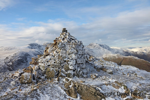 05D-9972 The Summit Cairn of Pike of Blisco in Winter with The Crinkle Crags and Bow Fell Behind Lake District Cumbria UK