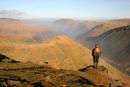 06-2214 Hill walker enjoying the view north over Brothers Water from Red Screes, Lake District, Cumbria