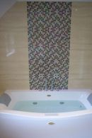 jacuzzi bath with mozaic tiling behind